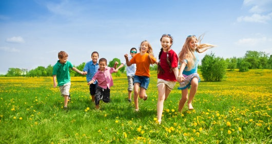 a group of children running together in a yellow flower meadow