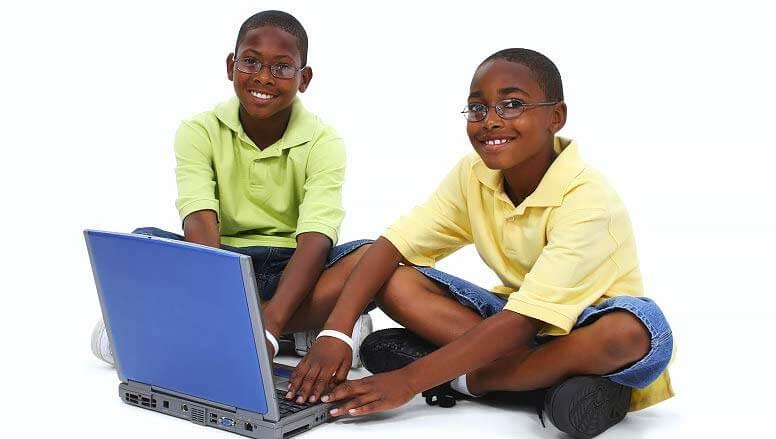 two kids using laptop