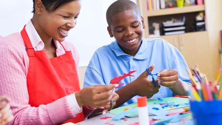 boy and teacher cutting art papers