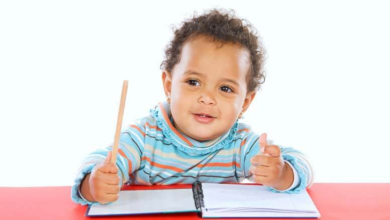 kid holding a pencil and notebook
