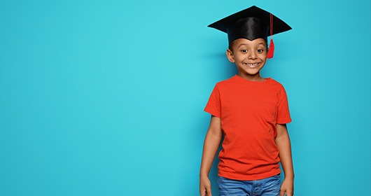 young-boy-graduate-smiling-on-blue-background